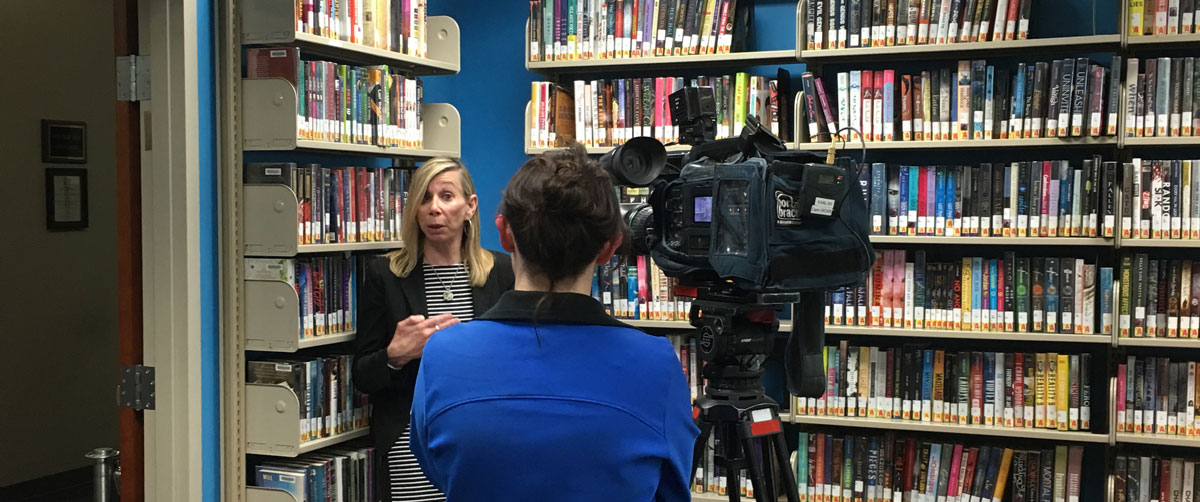 woman being interviewed in front of books, blue wall, interviewees back to viewer